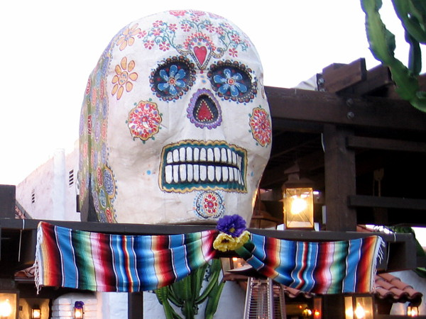 A large, colorful calavera above a restaurant inside Old Town San Diego State Historic Park.