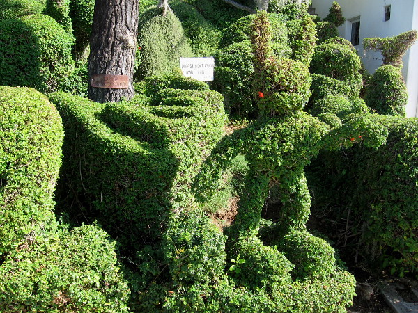 A funny rabbit stands and points among many topiary creatures.