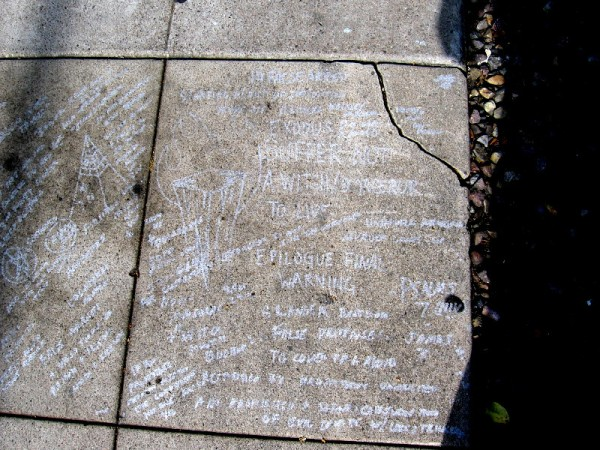 It appears someone scratched many warnings, symbols, theories and ideas on a section of the sidewalk.
