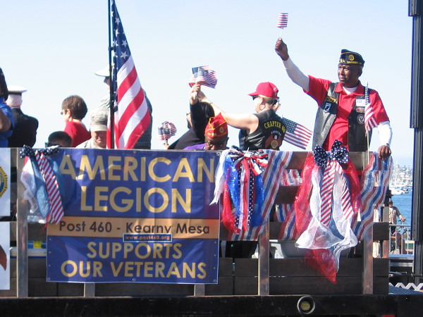 Flags raised high from the American Legion truck. They proudly support our Veterans.