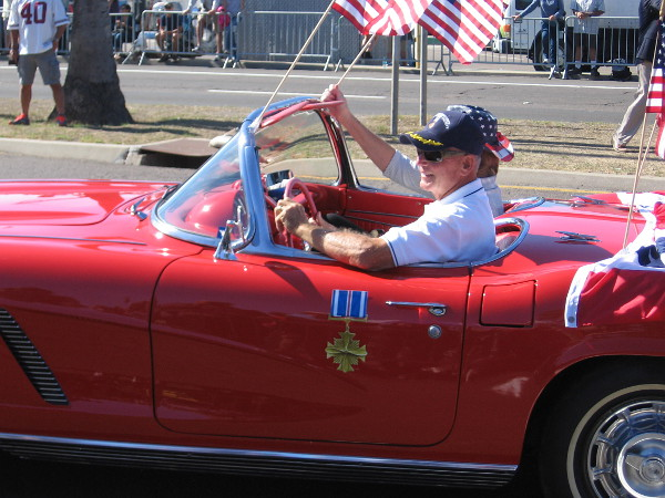 Member of the Distinguished Flying Cross Society passes in a classic car.