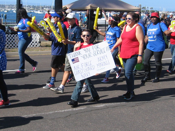 Kid holds a sign that reads Thank You For Your Service!!! Air Force - Army - Coast Guard - Marines - Navy