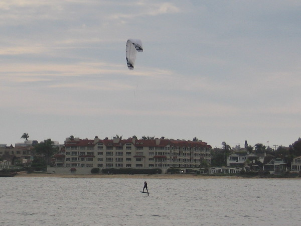 A distant kiteboarder, harnessing the chilly wind, rises above San Diego Bay.
