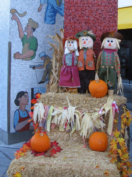 Three pumpkins and three smiling friendly scarecrows beside the base of the famous Little Italy landmark sign.
