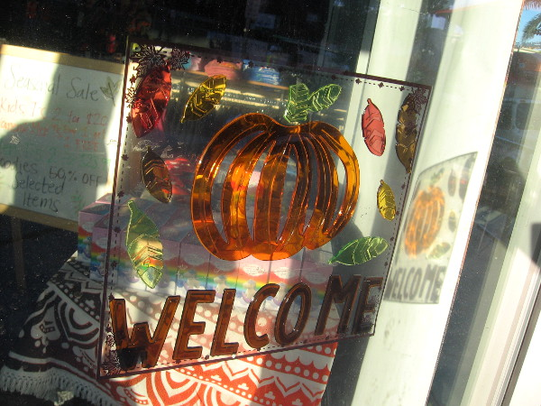A welcoming bright orange pumpkin in another shop window.
