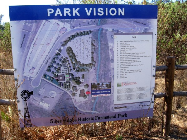 A sign shows proposed improvements to the Sikes Adobe Historic Farmstead Park, including event space and a reconstructed barn.