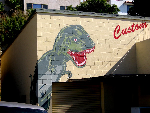 A colorful dinosaur on the building of Dyno Brand custom t-shirts!