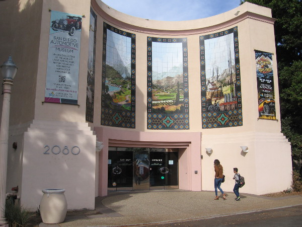 Visitors to the San Diego Automotive Museum in Balboa Park walk under four large temporary murals recently installed above the California State Building's entrance.