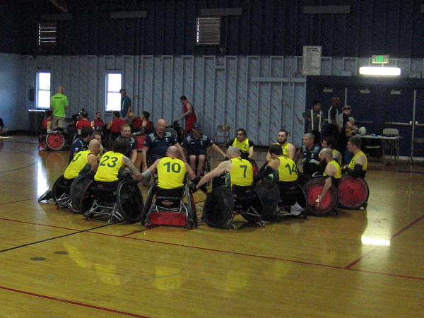 The victorious Australian quad rugby team celebrates by joining hands.