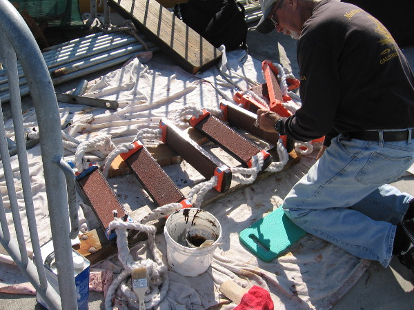 Elsewhere at the Maritime Museum, a volunteer adds paint to a newly acquired Jacob's ladder for the San Salvador replica Spanish galleon.