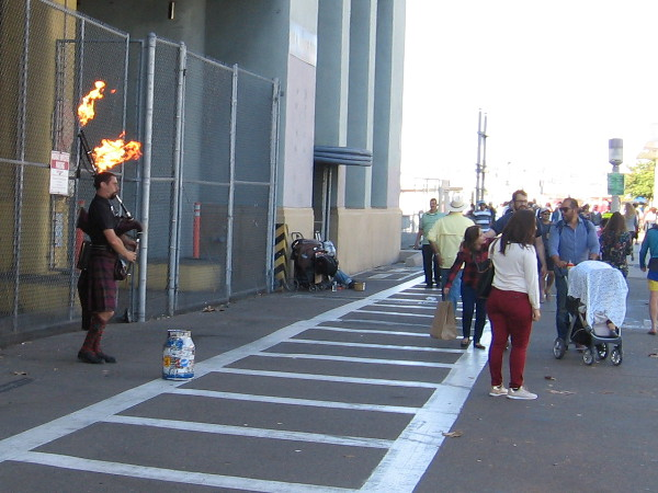 A street musician on San Diego's always dynamic Embarcadero plays bagpipes that shoot flames!