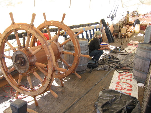 The ship's wheel has been removed and set to one side as the deck of the HMS Surprise is replaced.
