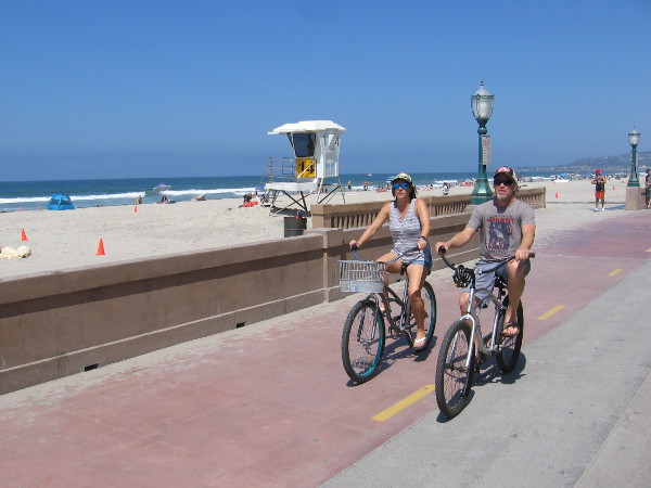 A couple rides bicycles along the Mission Beach boardwalk on a perfect day.