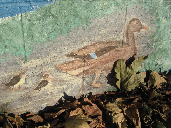 A mother duck and two ducklings walk among leaves on the Our River mural in Mission Valley.