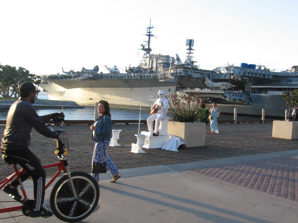 A busker and bicycle near the USS Midway Museum and Greatest Generation Walk.