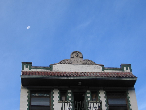 The moon in the sky above a historic building in the Gaslamp Quarter.