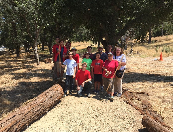Maxwell Thomson poses with friends among logs which now mark the trail through the revitalized USS Bennington Memorial Oak Grove!
