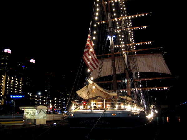 Photo of Maritime Museum of San Diego's famous Star of India, with magical holiday lights strung along masts, yards and rigging.
