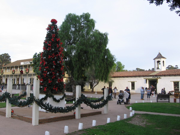 A big festive Christmas tree stands near the plaza's center, beside the tall flagpole.
