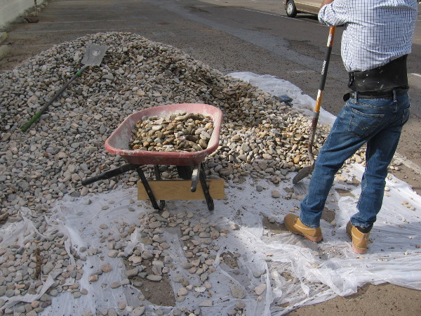 Shoveling weathered stones. Wheeling them about.