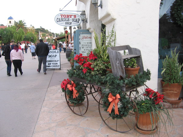 A colorful holiday wagon containing red poinsettias is parked outside Toby's Candle and Soap Shop.