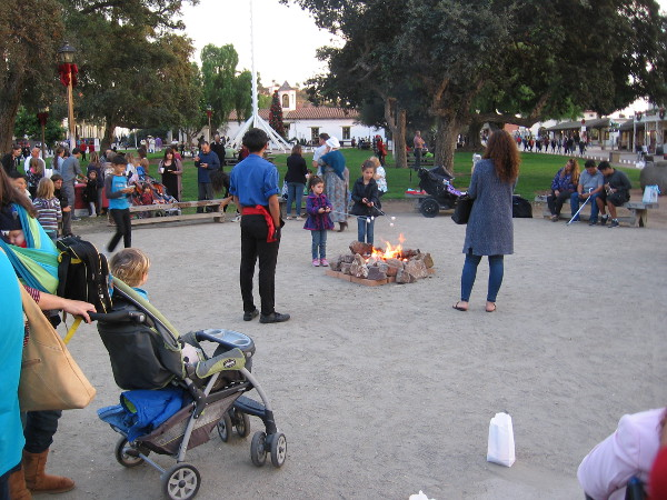 As daylight wanes, families congregate around a campfire and roast marshmallows for s'mores.