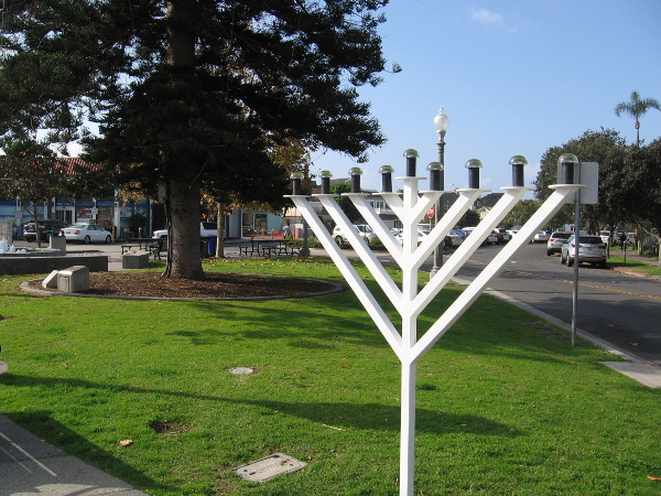 A Hanukkah menorah stands in Rotary Plaza during the holiday season. (The trunk of the large Coronado star pine Christmas tree is in the background.)