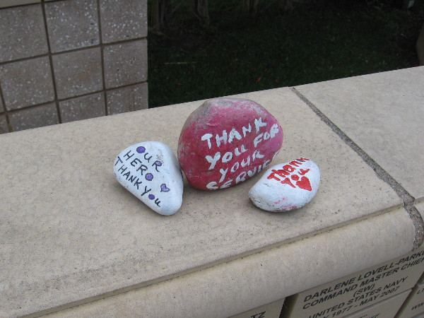 Painted on three small stones are words of Thank You for the service of heroes.