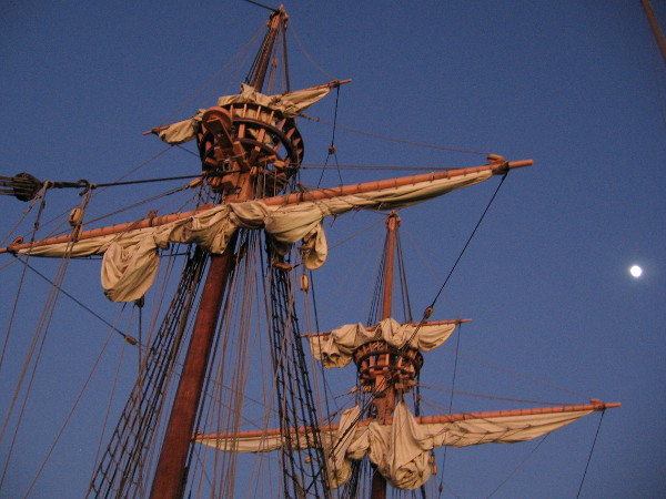 The last golden rays of sunlight strike the furled sails of San Salvador, under a nearly full moon.