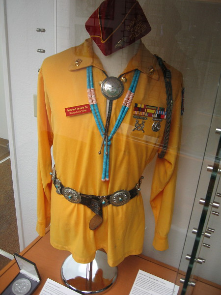 Official uniform of the Navajo Code Talkers includes a red cap, Navajo jewelry, gold shirt, patch on upper arm, light-colored trousers and abalone-colored shoes.