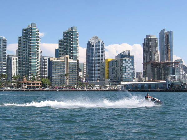 Riding recreational watercraft past the beautiful downtown San Diego skyline.