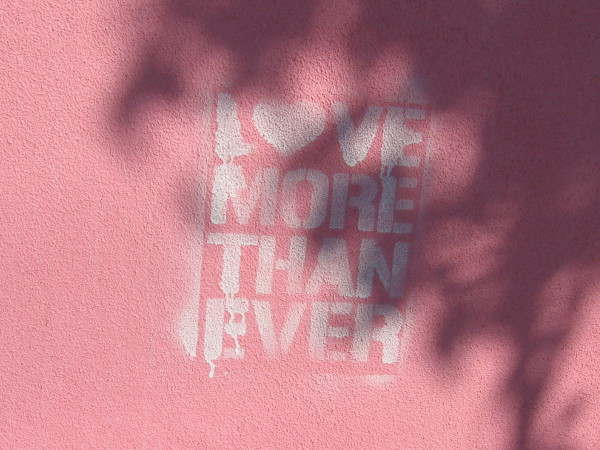 Love More Than Ever stenciled on a wall.