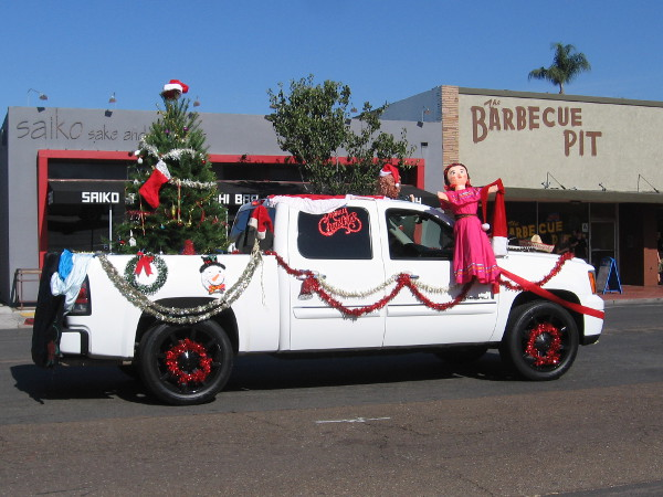 A fun truck with a Christmas tree in back.