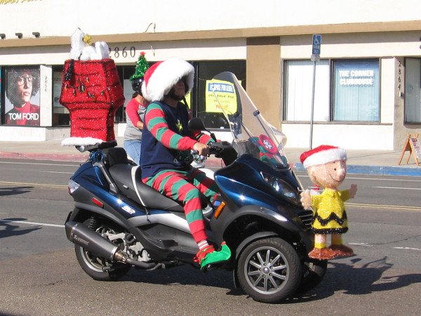 Here comes Charlie Brown, Snoopy and Woodstock on an elf-driven motorcycle!