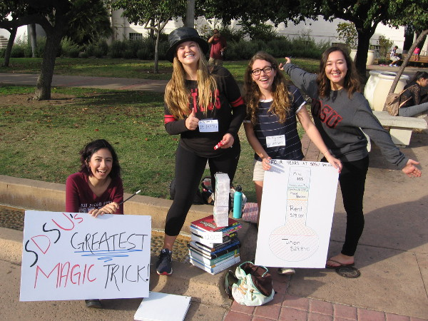 Friendly SDSU students perform a magic trick in Balboa Park. They demonstrate how high tuitions make money disappear!