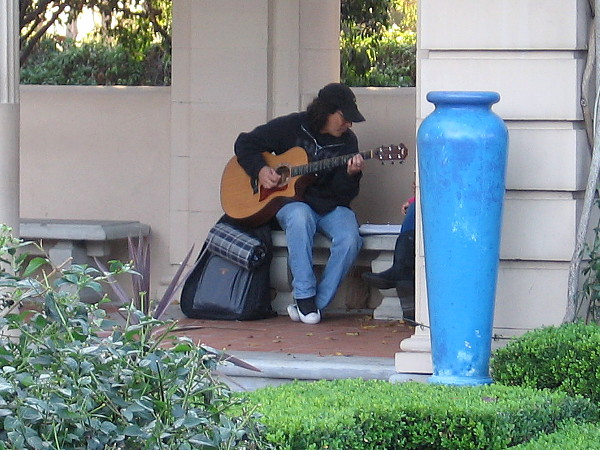 Playing guitar in a nook in the Alcazar Garden.