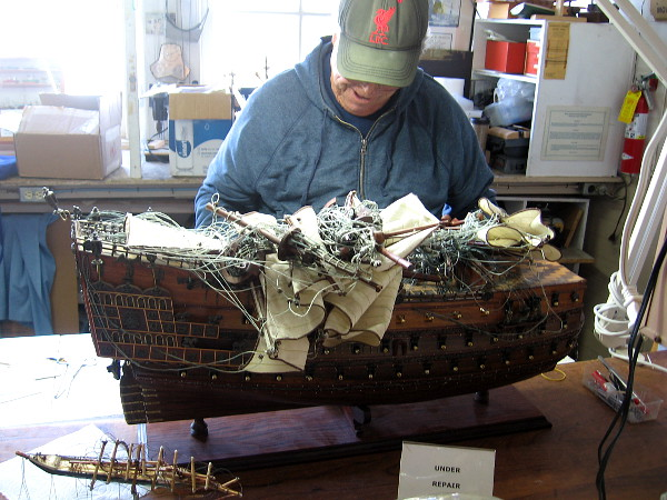 Detailed model of Sovereign of the Seas, a 17th century English Navy warship, is under repair at the Maritime Museum of San Diego.