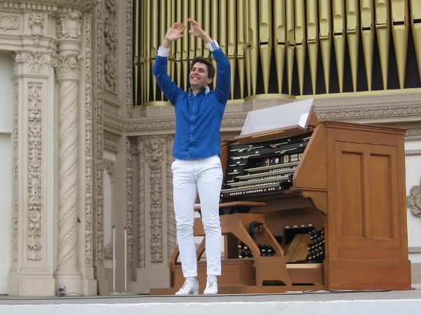 Raúl Prieto Ramírez, San Diego's new Civic Organist, raises his arms in greeting.