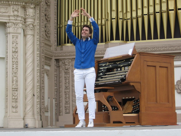 Raúl Prieto Ramírez, San Diego's new Civic Organist, raises his arms in greeting.