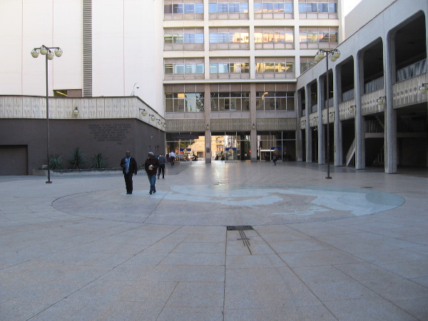 A few people stroll through Civic Center Plaza. Windows in the old (and many say outdated) City Administration Building rise over a passage to C Street.