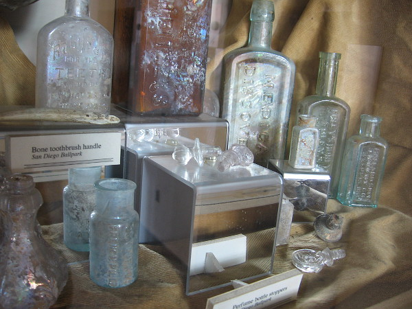 Excavated objects include jars, bottles, glass stoppers and a bone toothbrush handle. Names of medical remedies include Hamlin's Wizard Oil and Dr. J.H. McLean's Volcanic Oil.