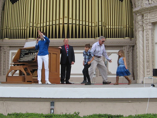 Kids from the audience take the stage right next to the Spreckels Organ console.