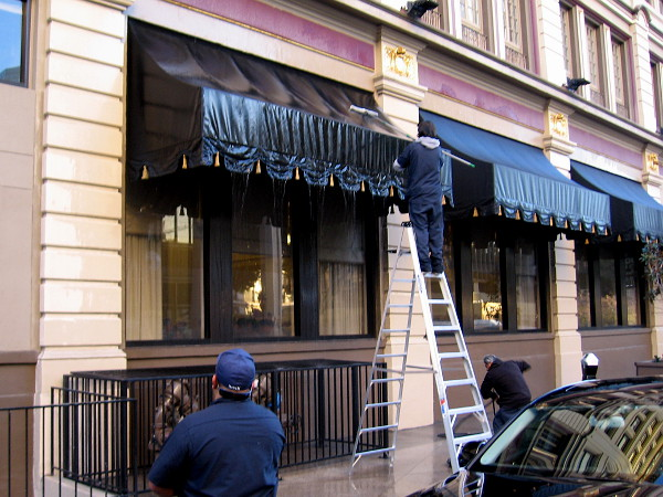 Workers were cleaning awnings over the ground floor windows of the U.S. Grant Hotel.
