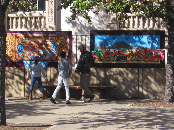 Visitors to Balboa Park check out a couple of the murals temporarily on display in the Plaza de Panama.