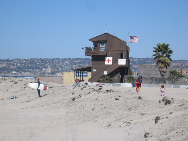 On the beach, a lifeguard building with flag flapping in the sea breeze. Pacific Beach and La Jolla rise to the north.