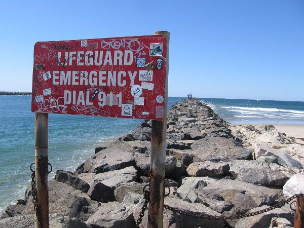 I stopped at the lifeguard emergency sign. Halfway down the jetty stands an old, abandoned bait shack, which appears like an arch that is covered with graffiti.
