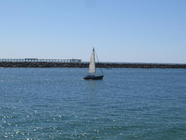Beyond this sailboat I see the Ocean Beach Pier.