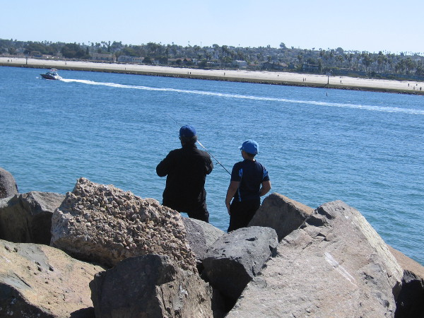 Several fishermen were casting into the blue water from the rocks.