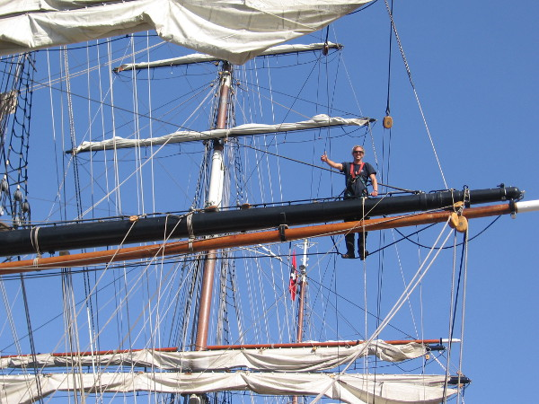 A wave from a crew member working high up on a yard of the beautiful three-masted clipper ship Stad Amsterdam.