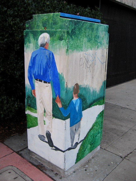 Street art in City Heights on University Avenue shows a father and son holding hands, walking down the sidewalk.